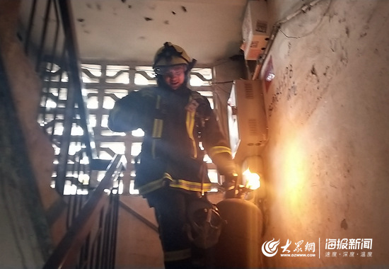 济南消防员徒手将冒火的煤气罐转移出火场。.jpg